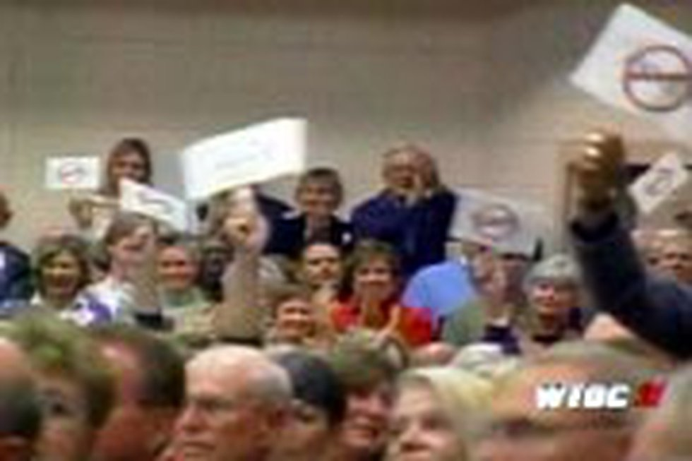 Residents wave anti-annexation signs at the meeting.