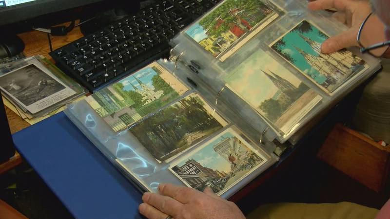 Tommy McDermott looks through a binder full of photos and postcards from Savannah's past.