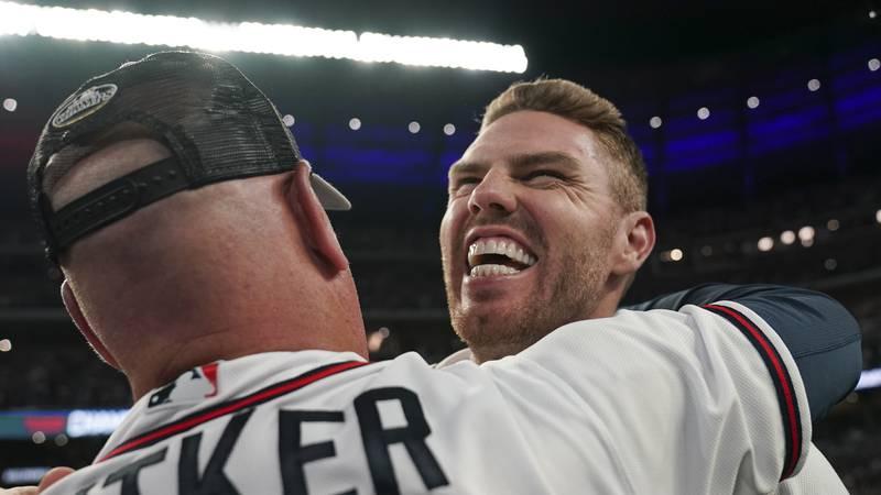 Atlanta Braves manager Brian Snitker hugs Freddie Freeman after winning Game 6 of baseball's...