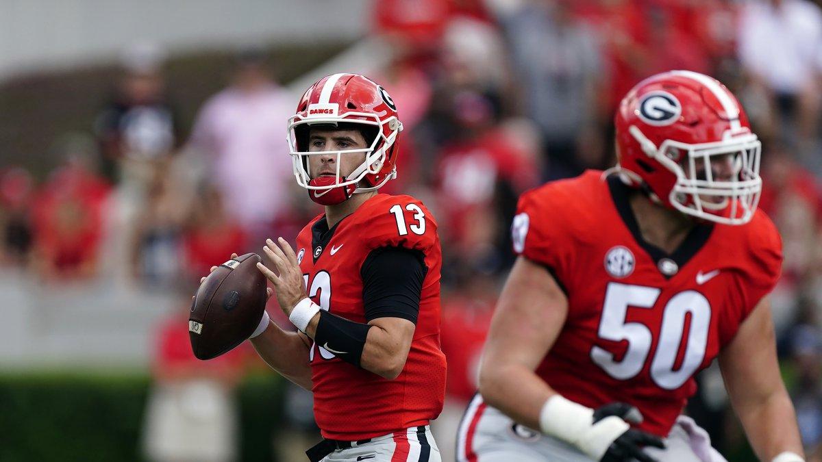 Georgia quarterback Stetson Bennett (13) throws behind offensive lineman Warren Ericson (50)...