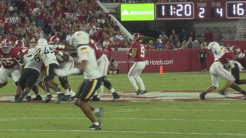 Bryce Young steps back for a touchdown throw