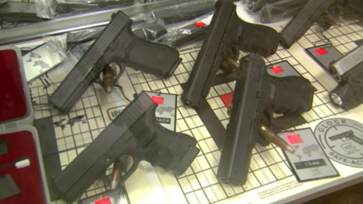Guns on a shelf in a store.