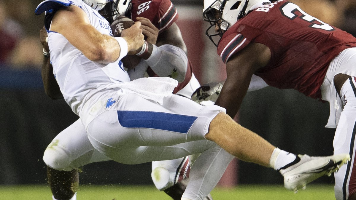 Kentucky quarterback Will Levis, front left, takes a hit by South Carolina defensive lineman...