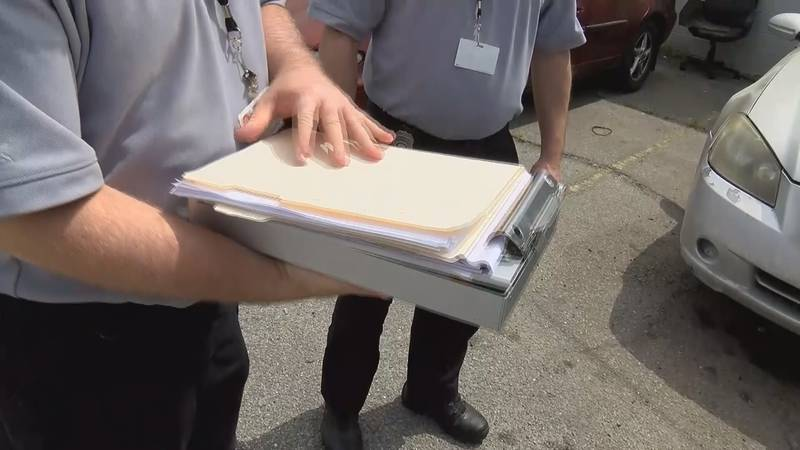 Code Enforcement Officers prepare to hand out a citation to a business that was deemed...