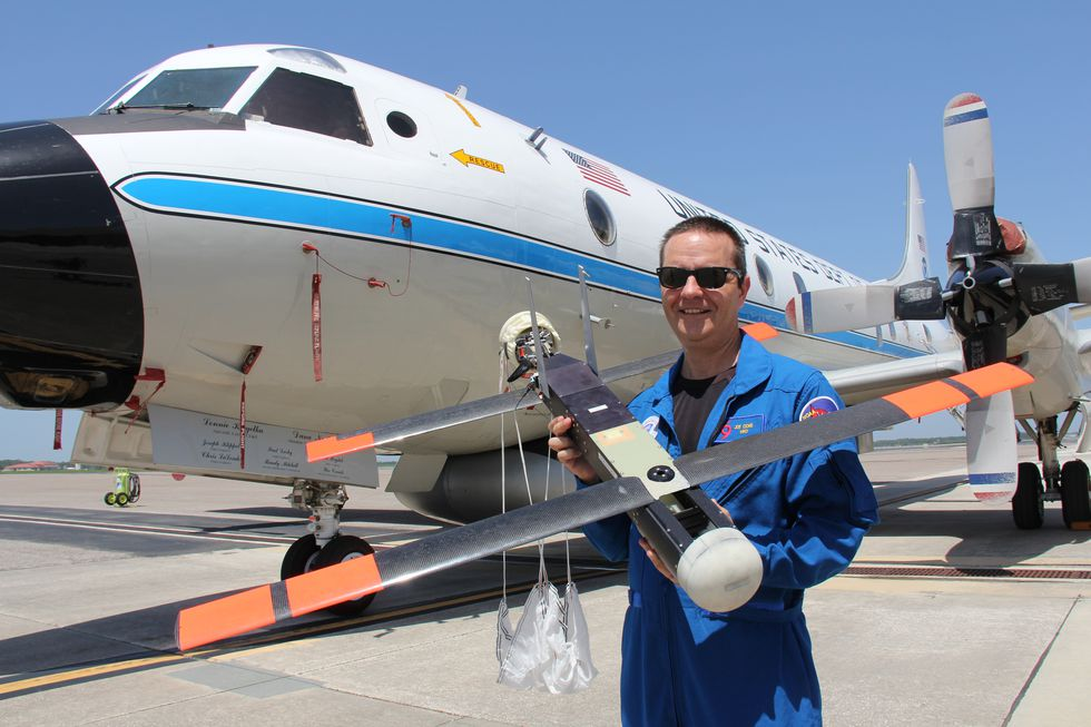 Dr. Cione holds a earlier model of a UAS in front of t P-3 Orion
