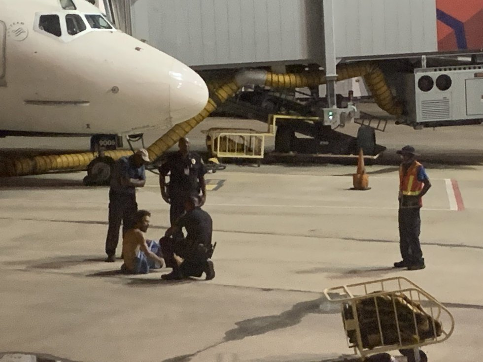 Police respond to naked man discovered under jet at