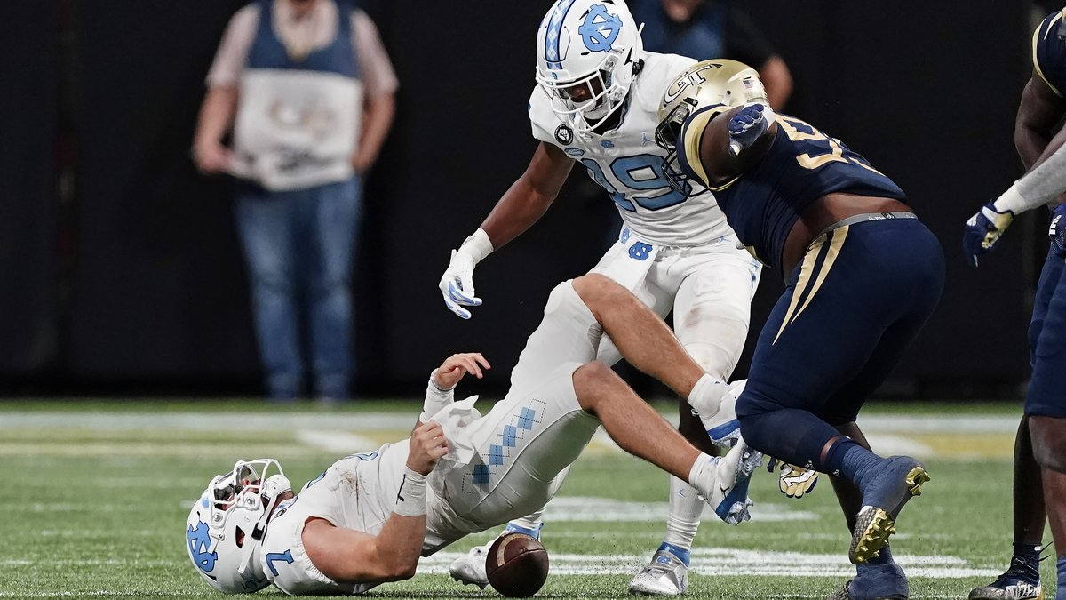 North Carolina quarterback Sam Howell (7) loses the ball after being hit by Georgia Tech...
