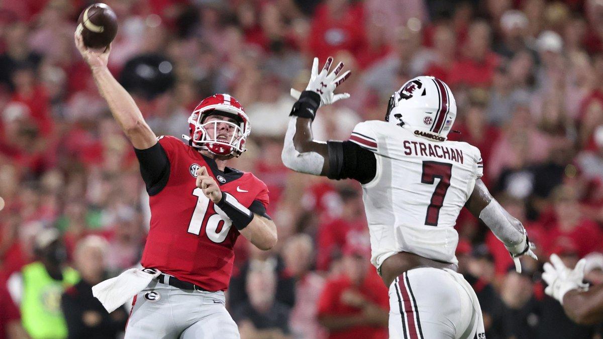 Georgia quarterback JT Daniels (18) throws a touchdown pass as South Carolina defensive end...