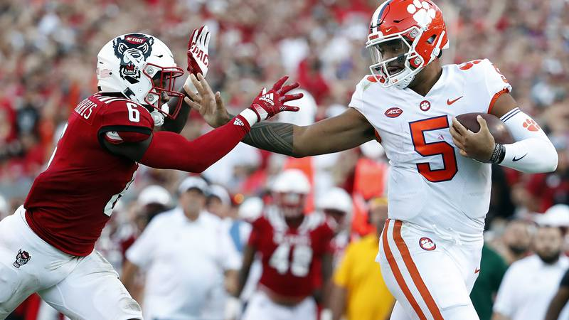 Clemson's D.J. Uiagalelei (5) stiff arms North Carolina State's Jakeen Harris (6) during the...