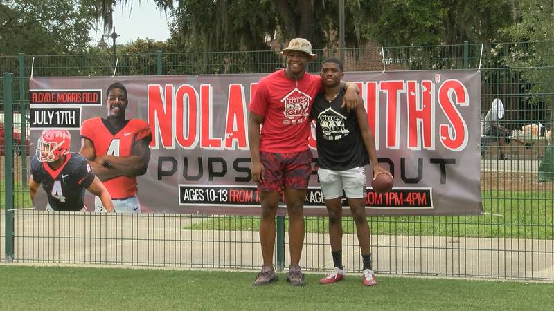 Georgia junior outside linebacker Nolan Smith poses with a camper at his first Pups Day Out...