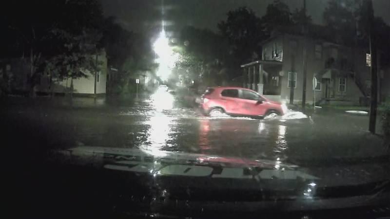 A car driving through a flooded Savannah street.