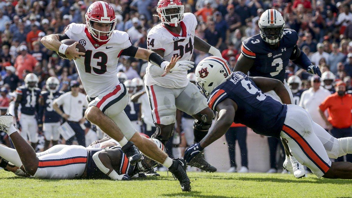 Georgia quarterback Stetson Bennett (13) carries the ball as he tries to get past Auburn...