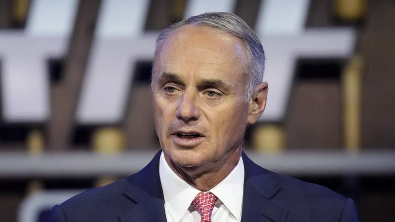 FILE - In this July 11, 2021, file photo, Major League Baseball Commissioner Rob Manfred kicks...